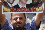 Demonštrant s fotografiou Mahmúda Ahmadinedžáda, Bašara al-Assada a Hassana Nasralláha. Zdroj: www.britannica.com