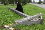 Kňaz nad poškodeným krížom. Zdroj: www.newsru.com